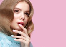 有轻的构成的美丽的女孩和在蓝色衣裳的柔和的修指甲 秀丽表面 设计钉子 免版税库存照片