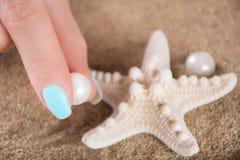 有轻轻地拿着珍珠和海星的蓝色修指甲指甲油的女孩手指 图库摄影
