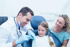 有辅助教的女孩的牙医如何刷牙 免版税库存图片