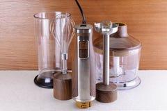 有辅助部件的木手搅拌器在木头和大理石backgrou 库存图片