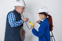 有辅导者的年轻女性电工 库存图片