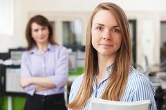 有辅导者的年轻女实业家在办公室 免版税库存照片