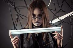 有辉光灯的美丽的机器人女孩在手中在样式计算机国际庞克 免版税库存照片