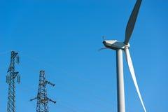 有输电线的风轮机 免版税库存照片