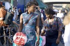 有辫子的两个女孩在美丽的礼服,在一个晴天努力去做在砖车道 库存照片