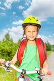 有辫子的微笑的女孩在自行车盔甲 库存图片