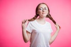 有辫子的滑稽的逗人喜爱的看在桃红色背景的少女和玻璃照相机 妇女佩带的白色T恤杉 免版税库存图片
