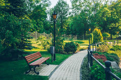 有边路和金属篱芭的空的夏天公园 库存照片