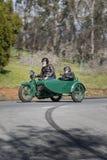 1923年有边车的哈利戴维森J摩托车在乡下公路 图库摄影