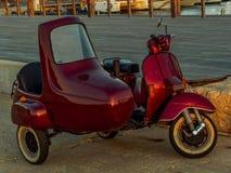 有边车的闪动的红色意大利滑行车 免版税库存照片