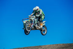 有边车跃迁的摩托车骑士从在蓝天背景的一座山  免版税库存照片