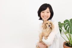 有达克斯猎犬的年轻亚裔妇女 库存照片