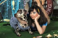 有达尔马提亚狗的年轻美丽的女渔翁 免版税库存照片