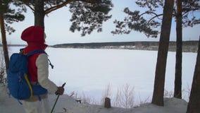 有迁徙在山的背包的女孩 冷气候,在小山的雪 高涨魔术其它短小冬天木头 有背包的一名妇女敬佩 股票录像