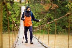 有迁徙在森林里的背包的人由在河的取决于的桥梁 冷的weathe 春天暴涨 木河上的桥 免版税图库摄影