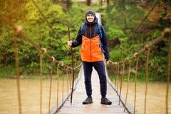 有迁徙在森林里的背包的人由在河的取决于的桥梁 冷的weathe 春天暴涨 木河上的桥 免版税库存照片