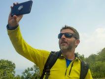 有迁徙的背包的年轻愉快和可爱的运动的徒步旅行者人远足在山采取selfie享受旅行逃走的 库存图片