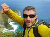 有迁徙的背包的年轻愉快和可爱的运动的徒步旅行者人远足在海峭壁采取selfie享受旅行逃走的 图库摄影