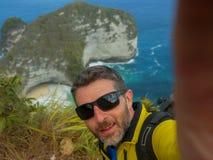 有迁徙的背包的年轻愉快和可爱的运动的徒步旅行者人远足在海峭壁采取selfie享受旅行逃走的 库存照片