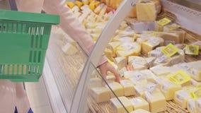 有过来对冰箱在商店和采取从它的购物车的少妇产品 在的女孩精选的乳酪 影视素材
