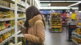 有过来对架子在商店和采取从它的购物车的少妇产品 美丽的女孩精选可口 影视素材