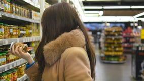 有过来对架子在商店和采取从它的购物车的少妇产品 美丽的女孩精选可口 股票视频