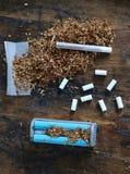 有过滤嘴的蓝色滚轧机和在烟草堆的一根手工制造香烟 库存照片