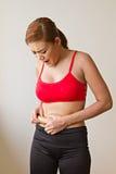 有过份油脂的不快乐的妇女在她的腰部 库存照片