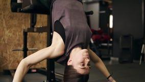有运作在她的吸收和核心肌肉的运动身体的坚强的嬉戏女孩使用特别健身房集合叫胃肠长凳 股票视频