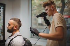 有运作在被弄脏的背景的发胶的年轻理发师 理发店理发师职业概念的时髦的客户 图库摄影