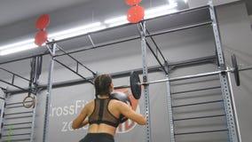 有运动服的行使与药丸的完善的健身身体的年轻坚强的妇女在健身房 做crossfit的女孩 库存图片