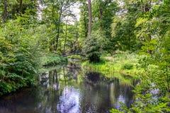 有运河和一座老曲拱桥梁的田园诗公园 免版税图库摄影