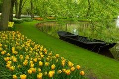 有运河和小船的春天庭院 免版税库存照片