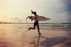 有运行到海的白色冲浪板的女子冲浪者 库存照片