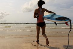 有运行到海的白色冲浪板的少妇冲浪者 免版税库存照片