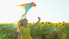 有运行在与风筝的黄色向日葵领域的长的红色头发的秀丽女孩 愉快的户外妇女 青少年 少年 股票视频