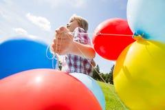 有运行在公园的五颜六色的气球的男孩 免版税库存照片