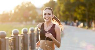 有运行在公园的耳机的快乐的妇女 免版税图库摄影