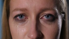 有运行在她的面孔下的染睫毛油的哭泣的妇女