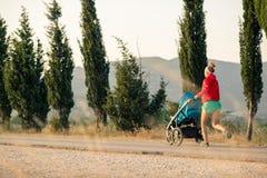 有运行在日落风景的婴儿车的母亲 图库摄影