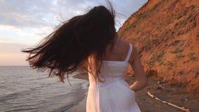 有运行在海滩的长发的美丽的浅黑肤色的男人在日落背景 股票视频