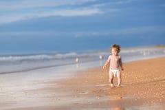 有运行在海滩的卷发的可爱的女婴 免版税库存照片