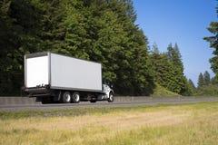 有运行在绿色路w的长的箱子拖车的大半船具卡车 免版税库存照片