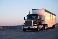 有运行在高速公路的大块拖车的黑暗的大半船具卡车  免版税库存图片