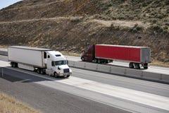 有运行在高速公路的拖车的两辆大半船具卡车  免版税库存照片