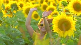 有运行在黄色向日葵领域的长的红色头发的秀丽女孩,举手 愉快的户外妇女 青少年 少年 股票录像