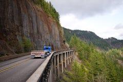 有运行平床半的拖车的蓝色大船具半卡车去 免版税库存图片