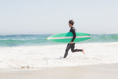 有运行往海的冲浪板的人 库存照片