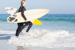 有运行往海的冲浪板的妇女 免版税库存图片