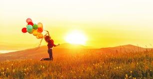 有运行横跨草甸的气球的愉快的快乐的女孩在sunse 免版税库存图片